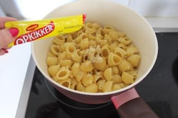 Giet de pasta af en voeg per persoon een zakje opkikker drink bouillon toe